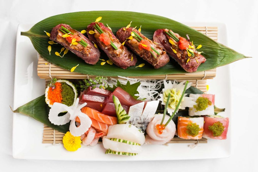 Top down photo of a two level sushi platter. Eight types of sushi are laid out on long green leaves and a white plate with white background