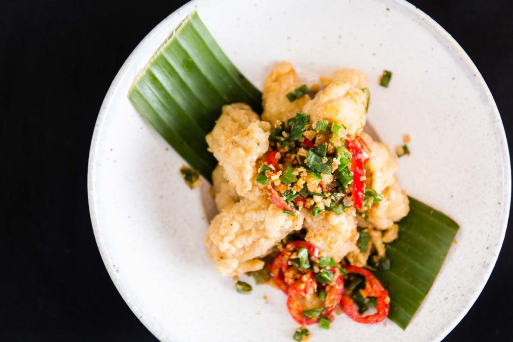 A top down photo of Thai scampi served on a white plate, green leaf with finely chopped red and green peppers with a black background