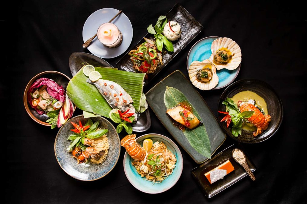 Top down shot of ten Thai dishes on separate plates in a black background. Scallops in shells, lobster tails, hake, King prawns, salads, white fish, desserts and lamb with rice