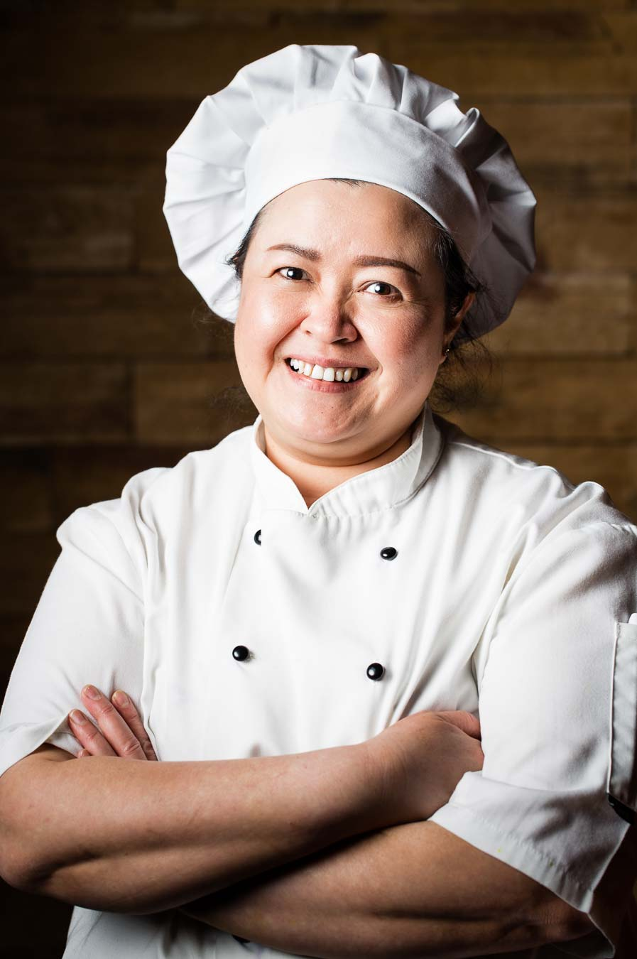 Thai female chef portrait wearing whites and a chefs hat with a wooden background