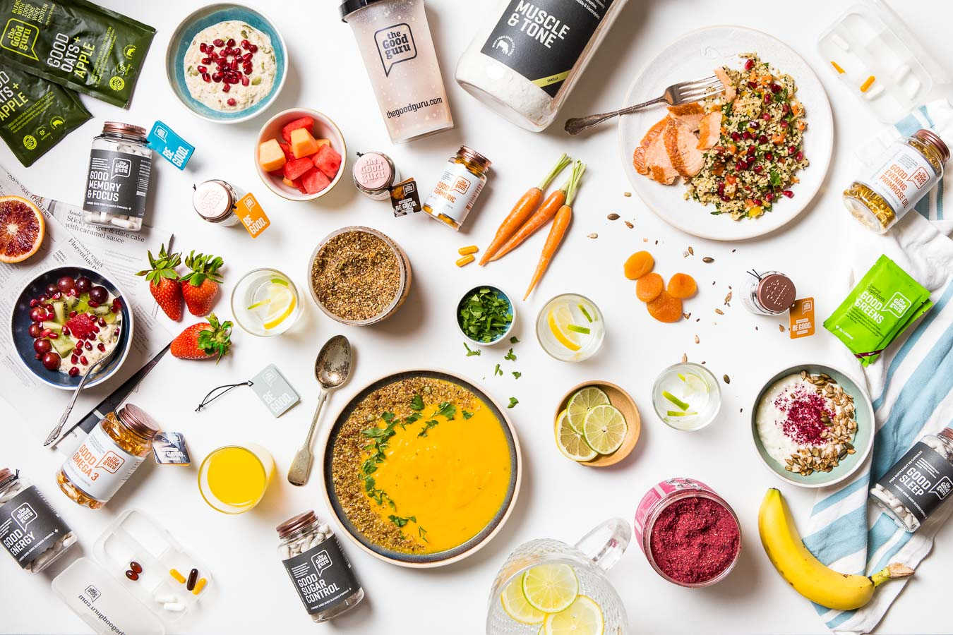 Flat lay of The Good Guru health products in the bottles, fresh strawberries, banana, mini carrots, bowl of yellow soup, seed and fruit breakfast bowls