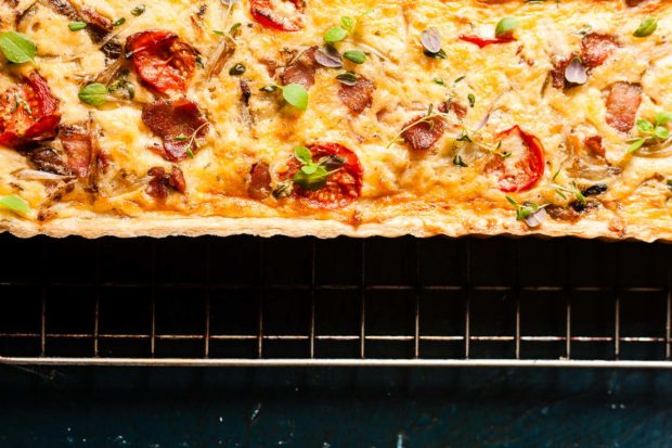 Tomato and bacon baked quiche with green micro herbs on a cooling rack on a dark blue rustic background