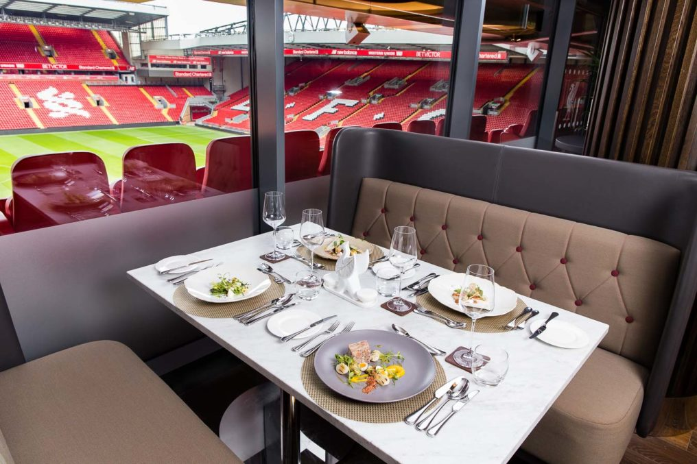 The fine dining table layout of the trophy room dining tables at Liverpool Football Club, with four plated dishes and a raised view of the Anfield football pitch and surrounded seating
