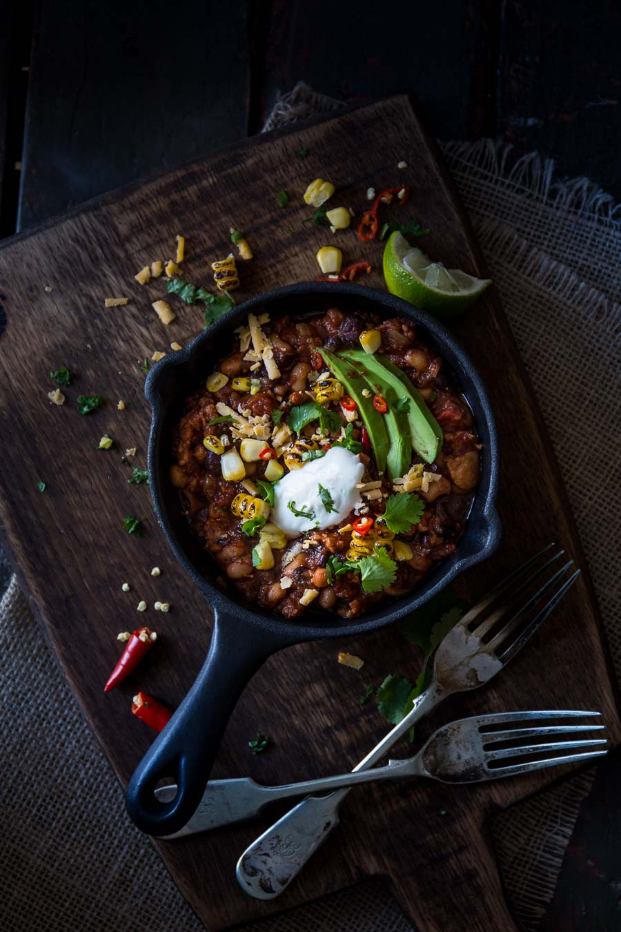 A black cast iron skillet containing turkey chilli, sweet corn, avocado and herbs, sits on a rustic wooden chopping board with textured textiles and forks