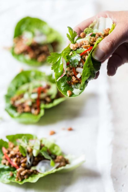 Someone holds a lettuce cup filled with turkey mince, fresh herbs and finely sliced red pepper with other lettuce wraps in the background