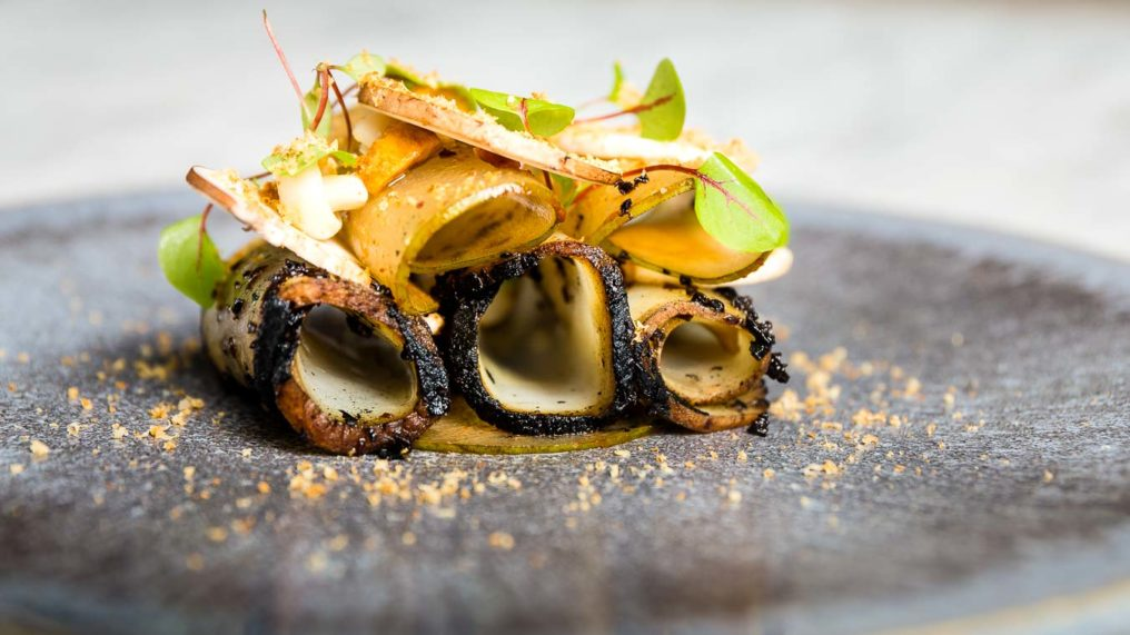 Fine dining from The Typing Room of potato rolled into tubes and blackened edges, laying on their sides, dressed with micro herbs and mushrooms on a grey textured plate