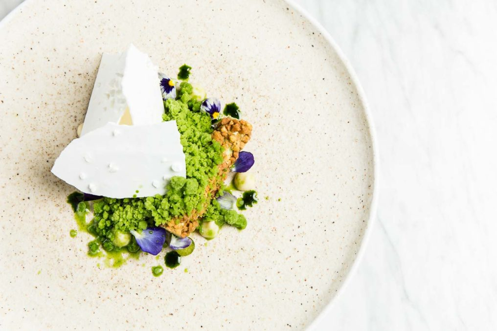 Fine dining plated dessert with white wafers hiding the ice-cream with a green crumb and edible flowers. The plate is white with speckles with a white marble background