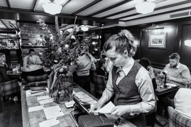 Female front of house staff using the ordering system in the dining room of The Oxford Blue Pub, Windsor by Chef Steven Ellis