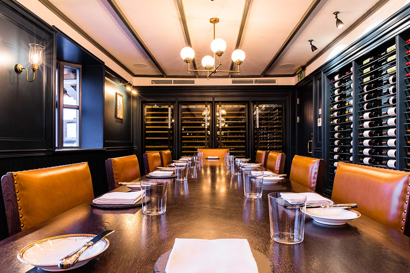 A long, wooden table stretches out lined with rich blown leather chairs, place setting all along the table. The open wine rack lines the right hand wall of the wine attic at The Oxford Blue Pub and four wine fridges can be seen at the far end of the room which is lit be wall and ceiling lights