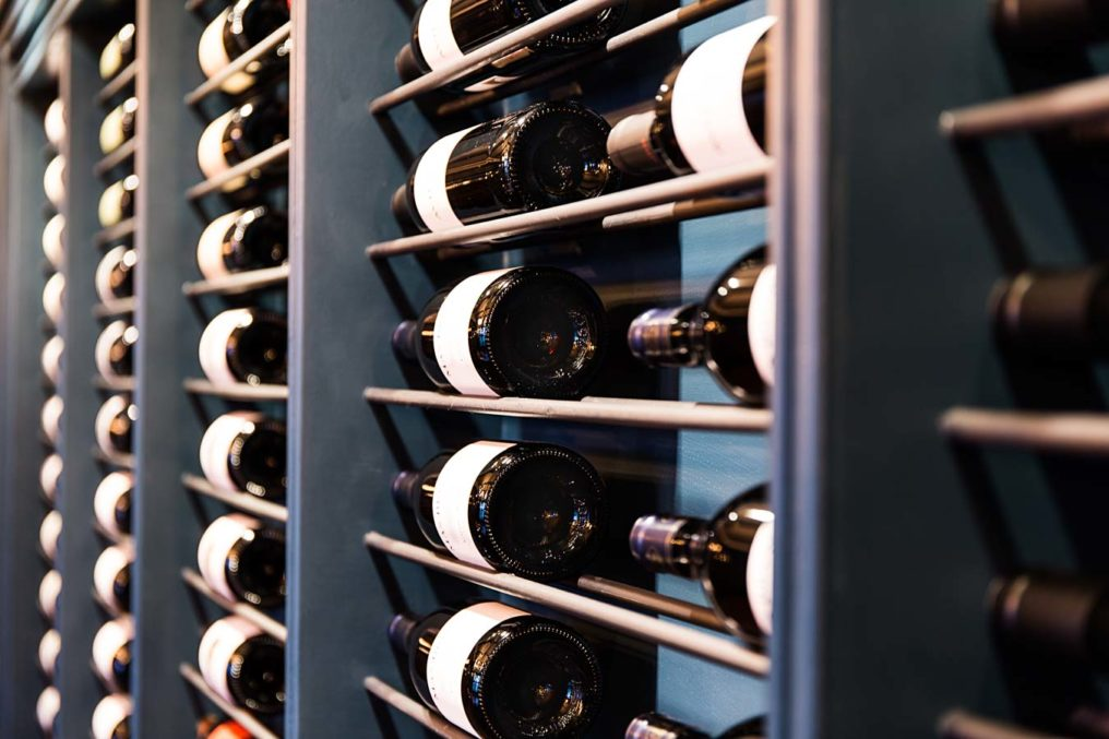 An angled shot of a blue wine rack which is the full length of the wall, filled with bottles of wine