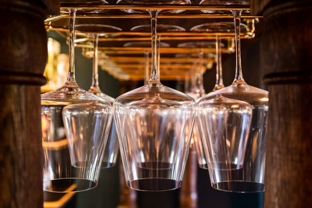 Close up shot of long stem, wine glasses hanging upside down in glass holders at a traditional English bar