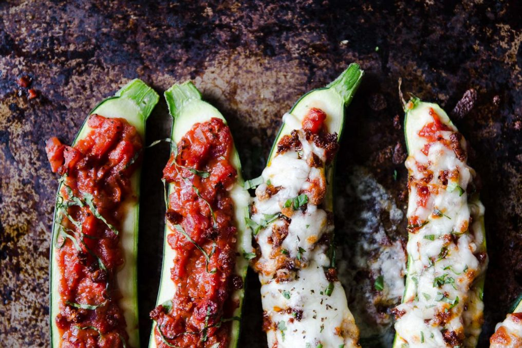 Halved roasted zucchini filled with tomato sauce and cheese sit on a rustic baking sheet
