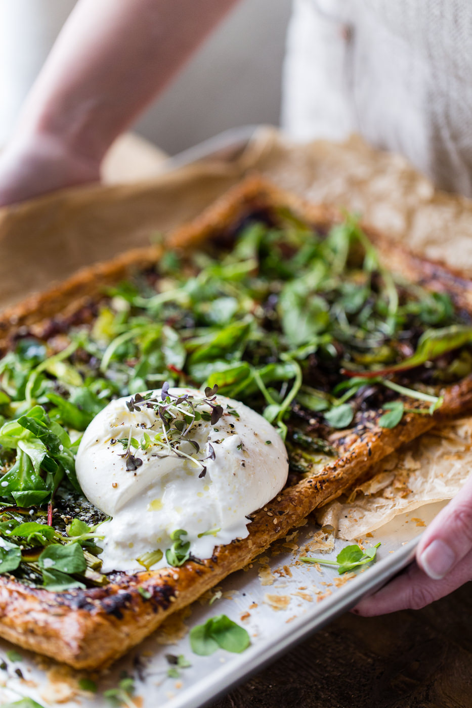 A baking tray, being held by someone, with parchment paper and a roasted vegetable, puff pastry tart with green micro herbs and a full round burrata cheese which has been cut open and is oozing out