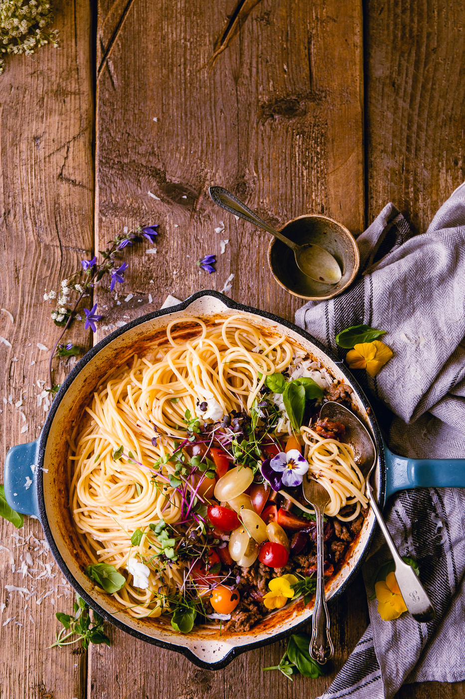 Top down photo of spaghetti, tomatoes and a bolognese sauce cooked in a blue and white cast iron skillet, garnished with herbs with a black and white textile on a rustic wooden table top