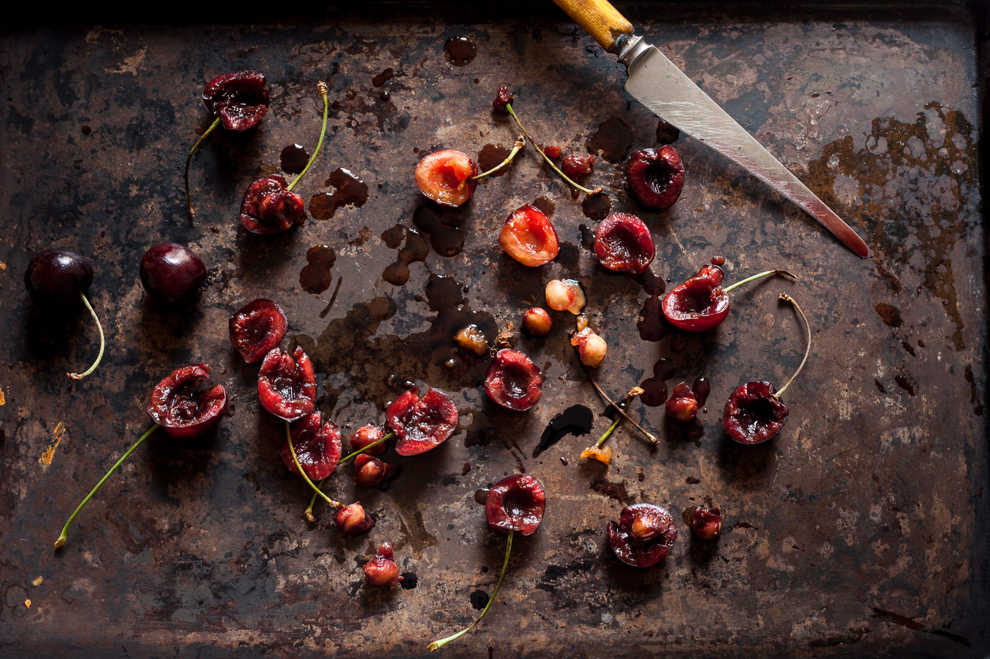 Sliced cherries on a rustic baking sheet, the knife can be seen to have cherry juice along it and juices are on the baking sheet
