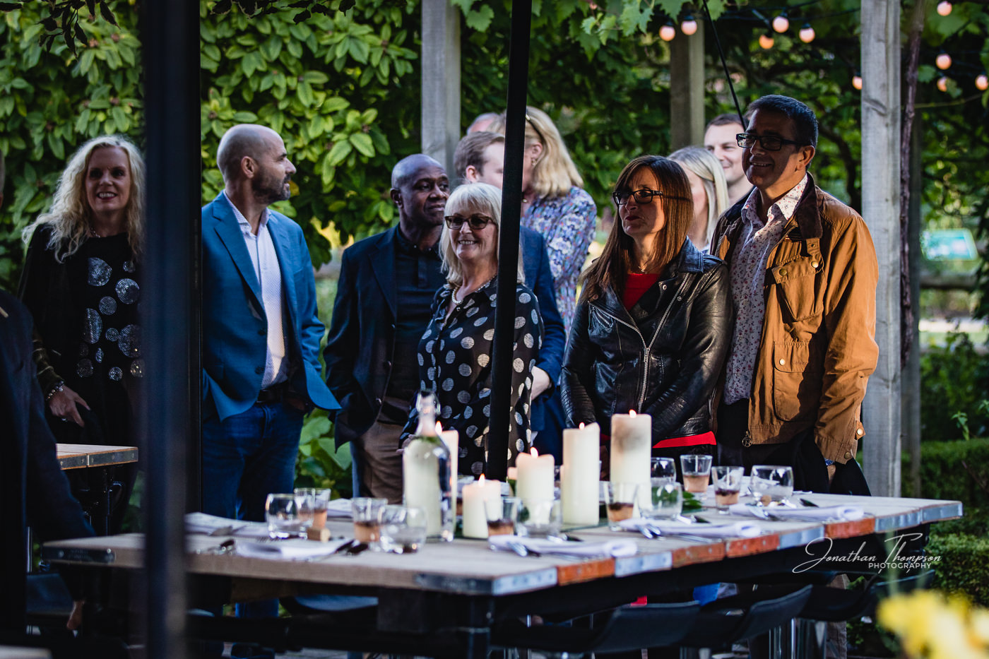 Guests waiting to be seated at an outdoor dining event at Chester Zoo. The table is set for dinner with glasses and candles