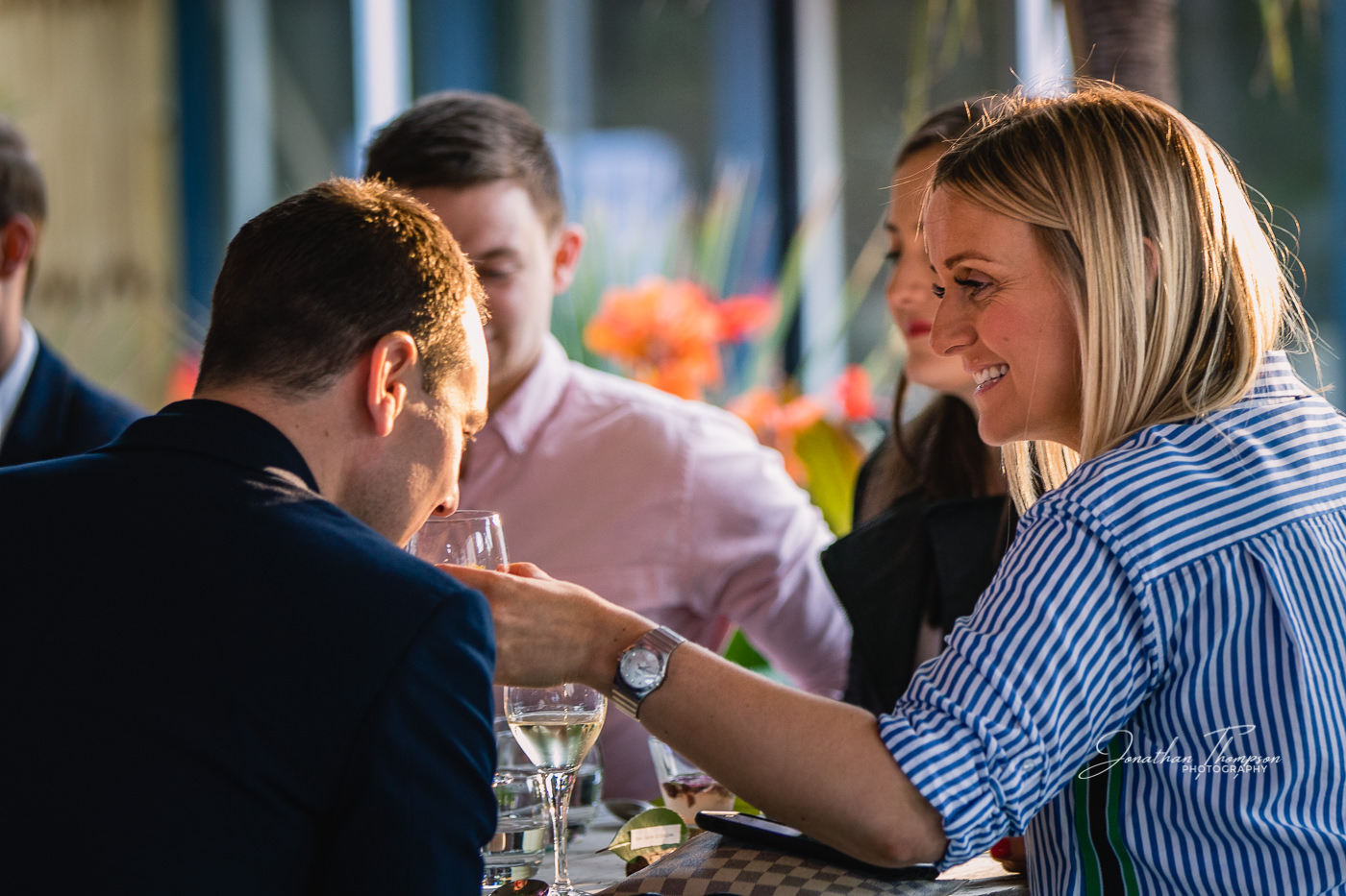 Blonde lady holds out her wine glass so the man next to her can smell it, in an outdoor dining scene at Chester Zoo