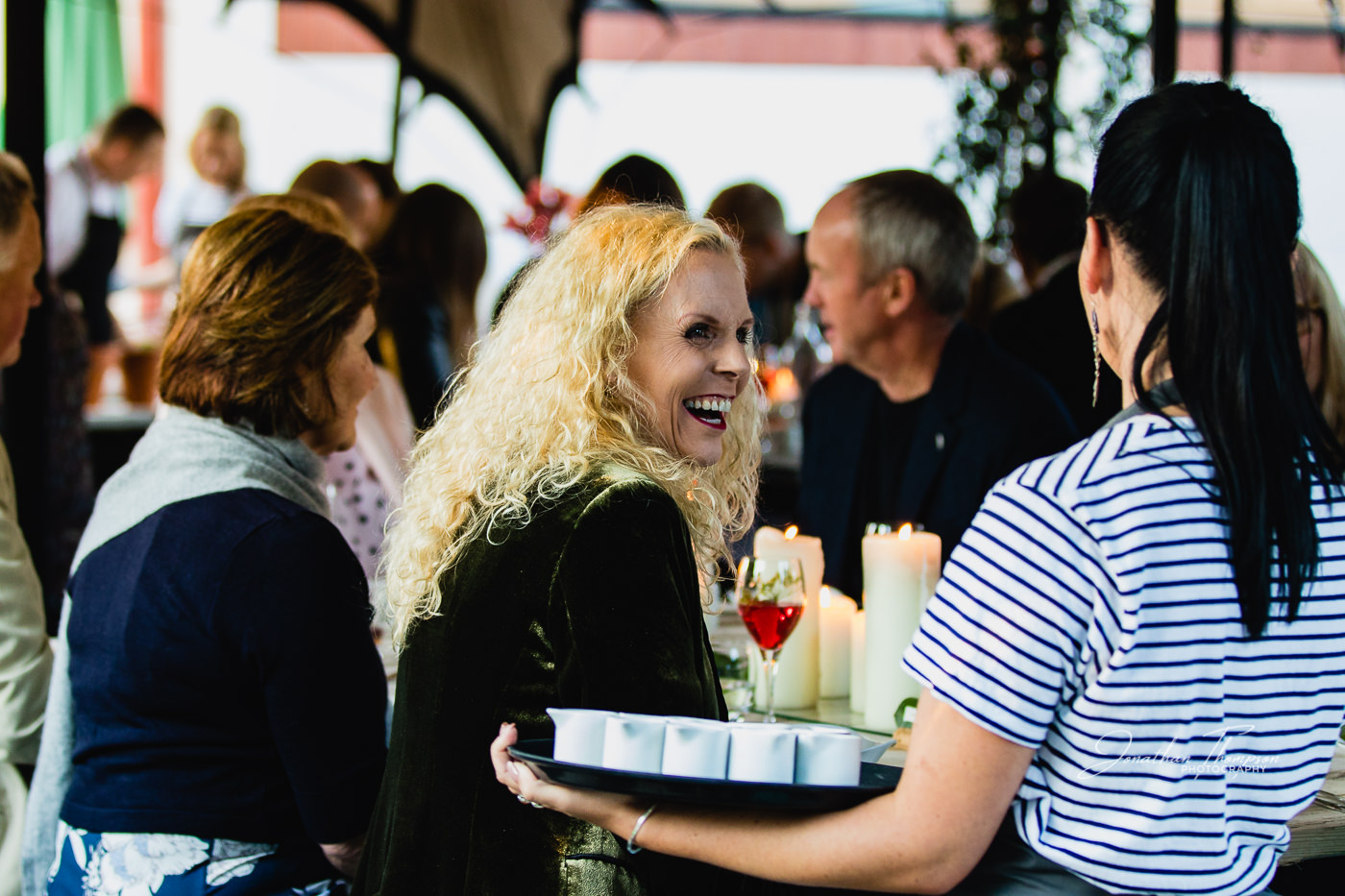 Blonde haired lady turns to her waitress with a big smile. In an outdoor dining event. Chester Zoo
