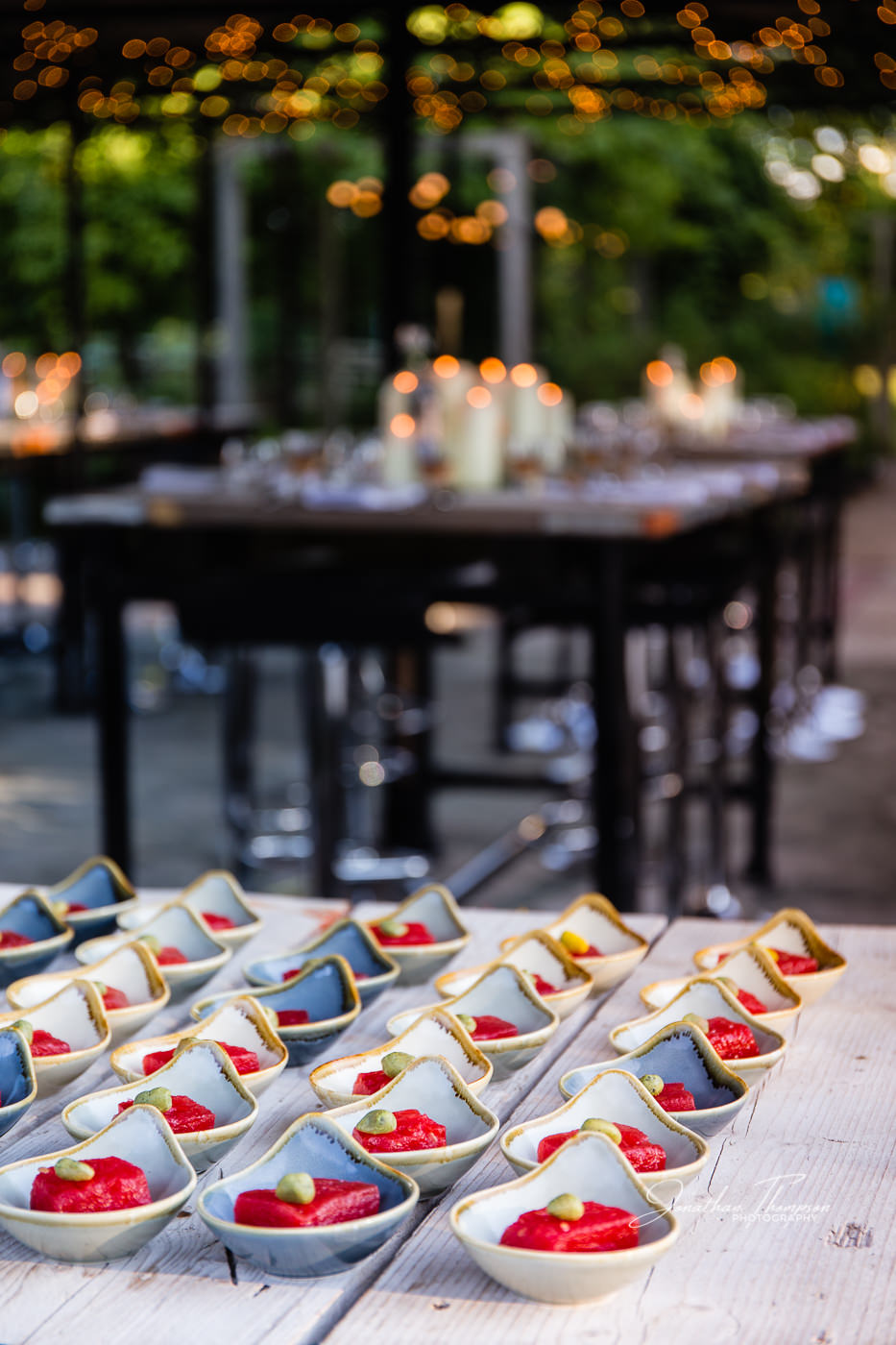 Small blue dishes are lined up with red and green food in an outdoor dining venue at Chester Zoo