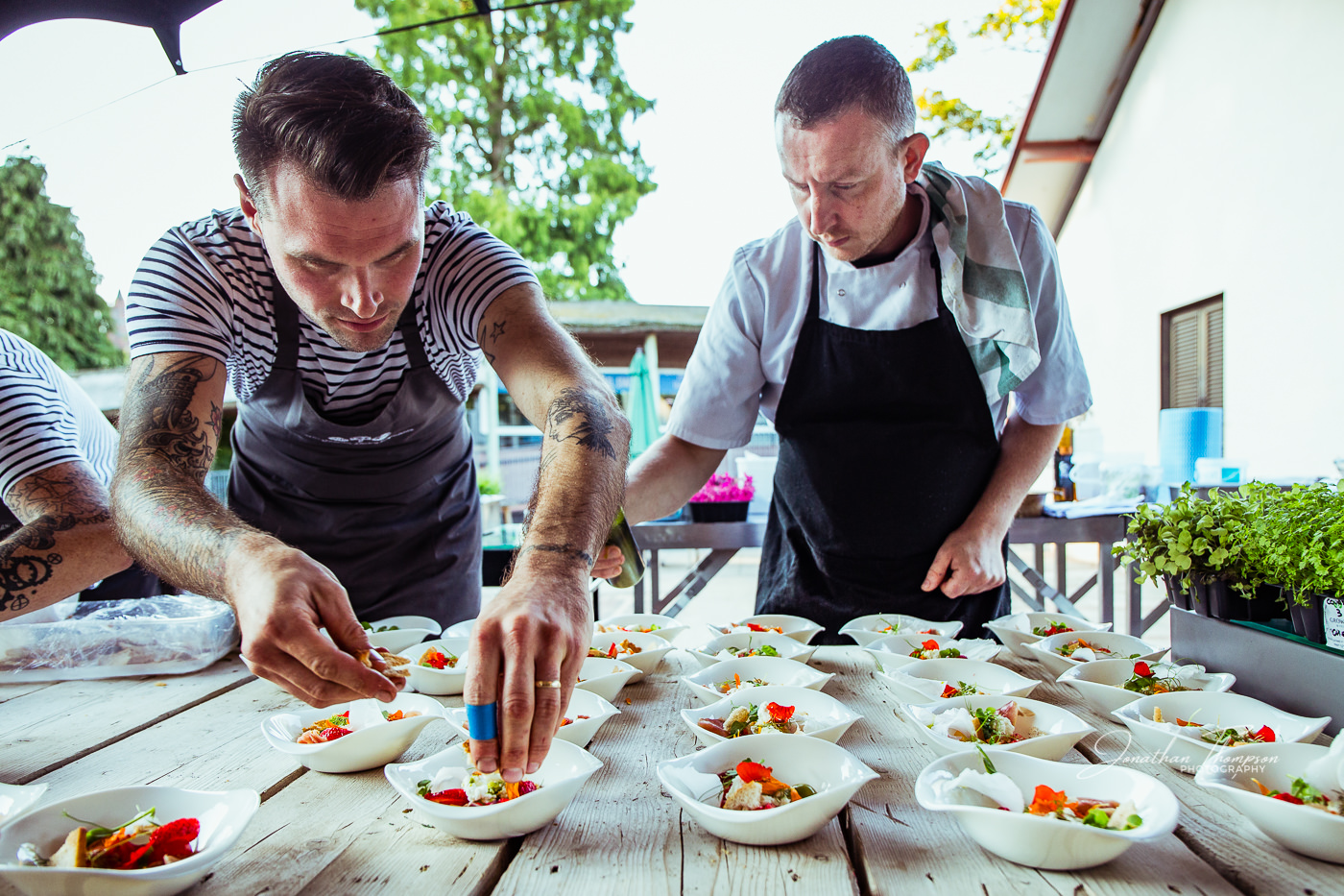 Male chefs are carfully plating up a salad in white bowls in an outdoor venue at Chester Zoo