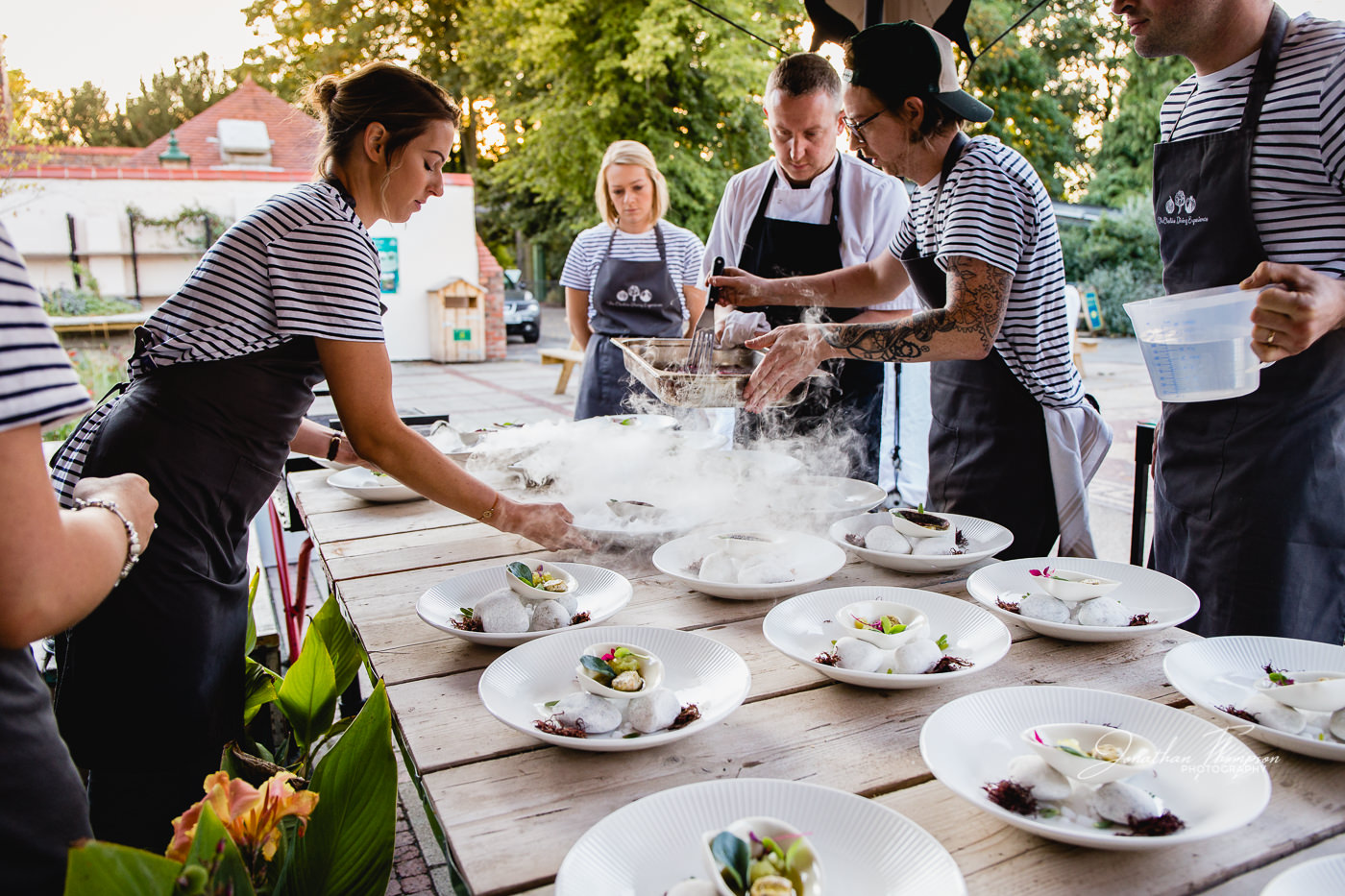 Chefs plating up rows of white plates in an outdoor setting while wait staff pick up finished dishes to serve. Chester Zoo
