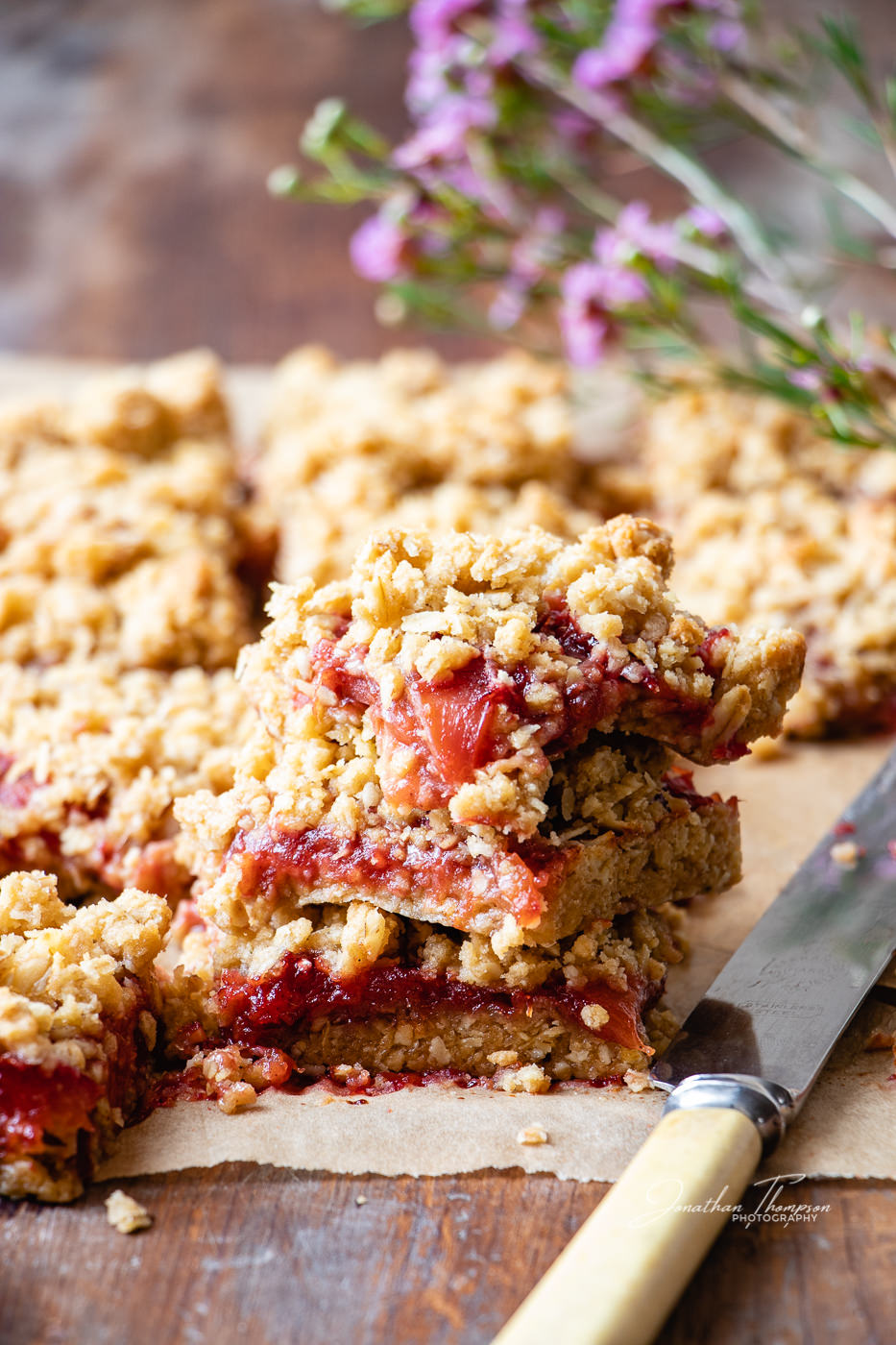 Fruit crumble bar with small pink flowers in the background