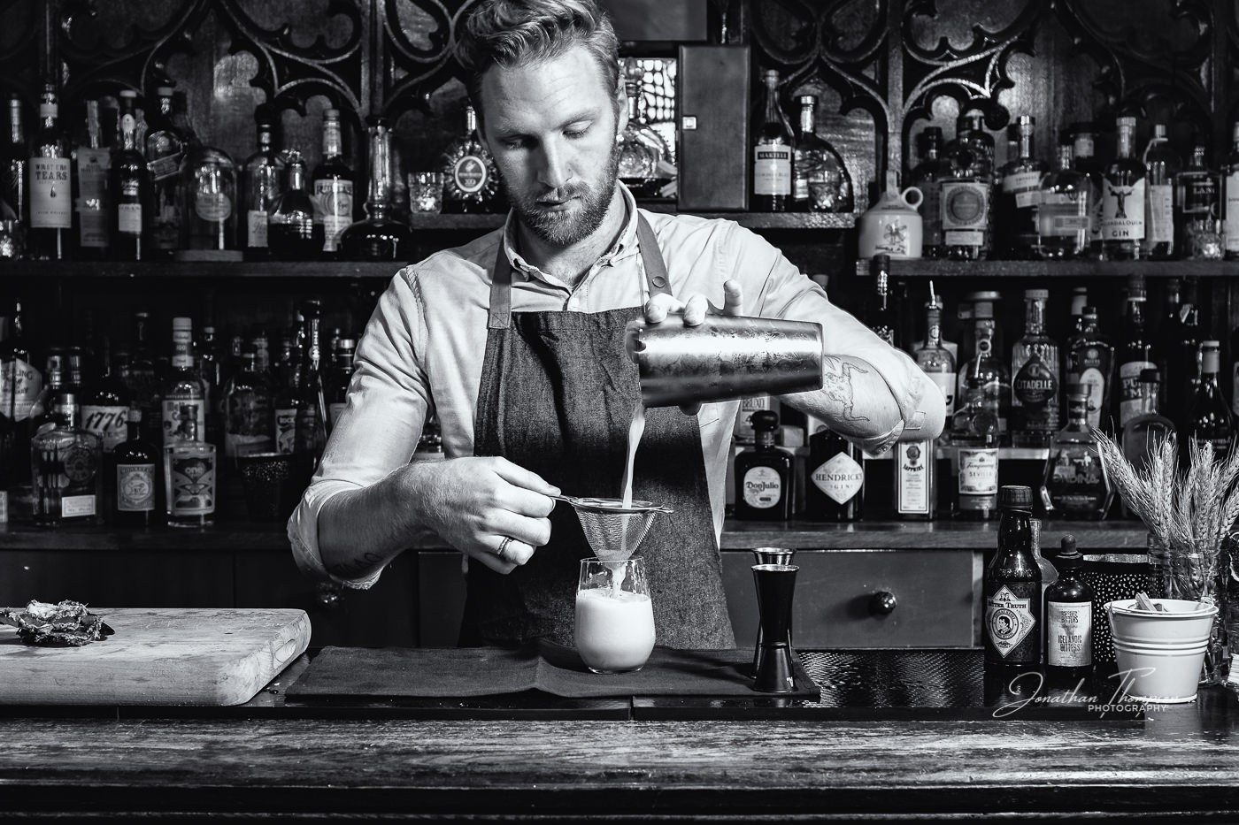 A black and white of Calum Adams, a mixologist, pouring a cocktail from the shaker through a sieve into a glass