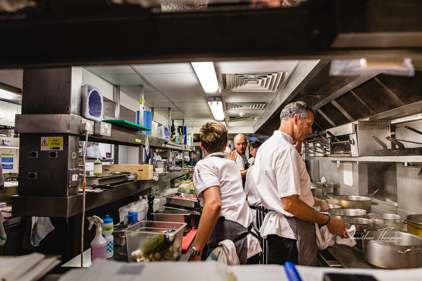 Viewed through the pass, Chef Phil Howard standing calmly at the stove whilst behind him two chefs reach towards each during service.