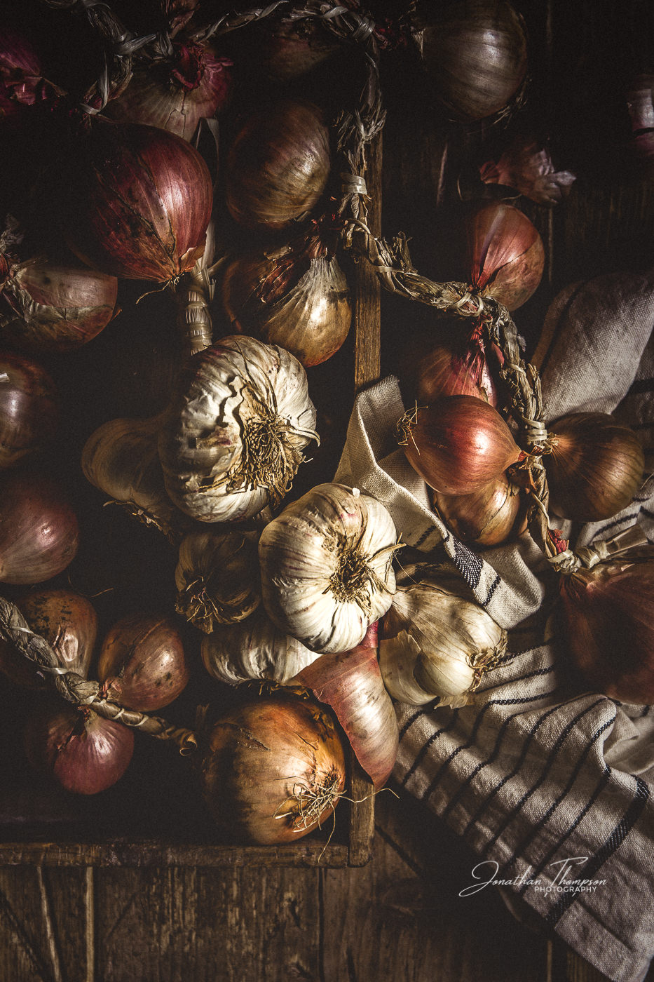 A fine art photograph from personal projects of onions and garlic in their rustic state with lots of textures and soft light.