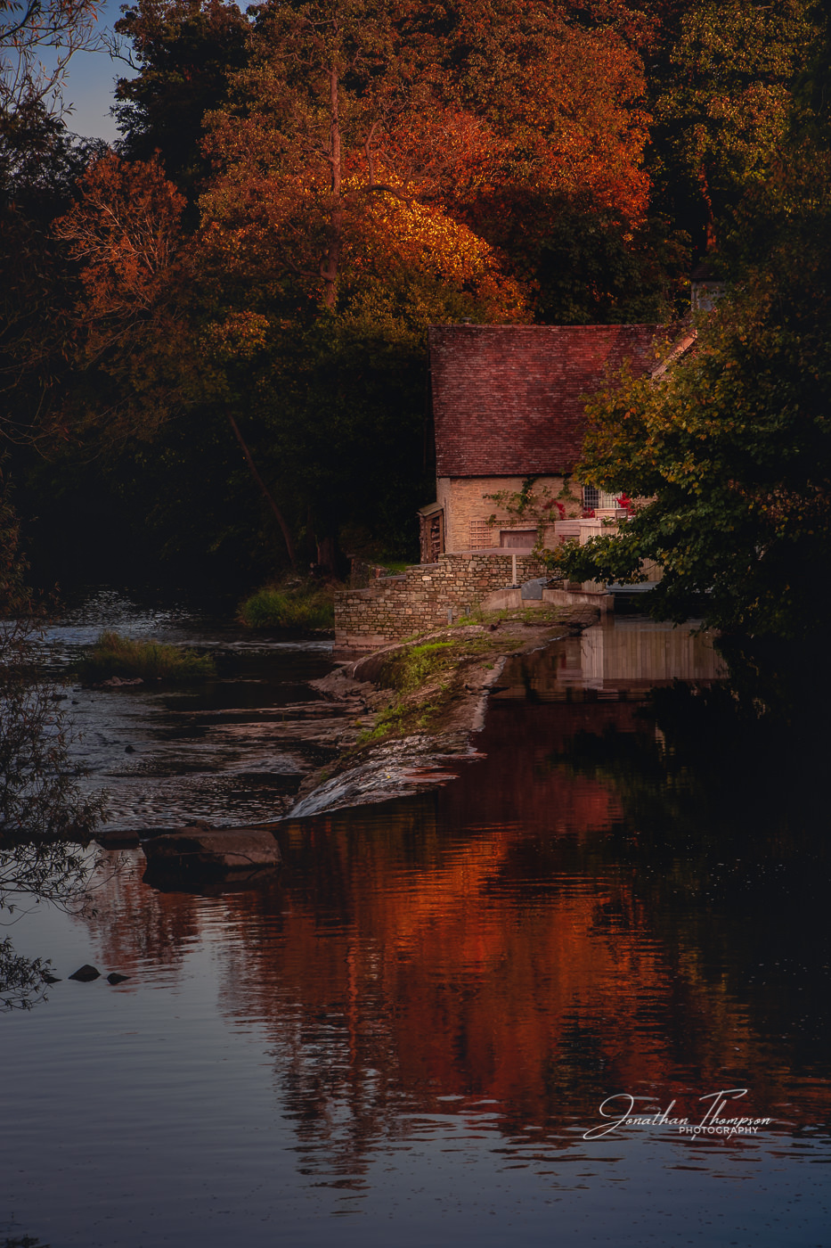 An Autumal Fall river scene with a stone cottage surrounded by orange and red leafed trees on the edge of a river. The colors are reflected in the water. Travel Photography
