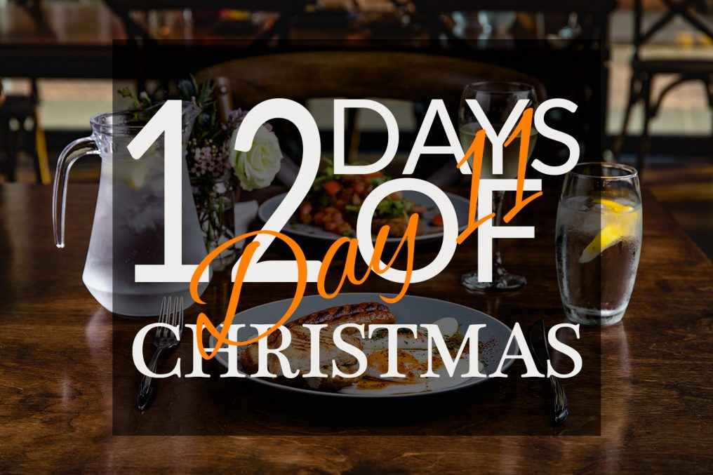 A restaurant scene from The Kitchen at Storyhouse, Chester. Two table setting opposite each other, the nearest plate has a cooked English breakfast. There are drinking glasses and a jug of cold water. With a graphic overlay saying 12 Days Of Christmas-Day 11