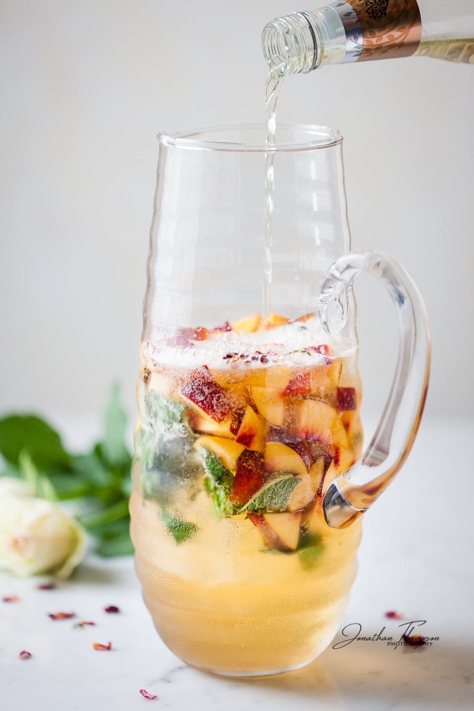Clear liquid pouring into a glass jug containing fruit juice, fruit and mint