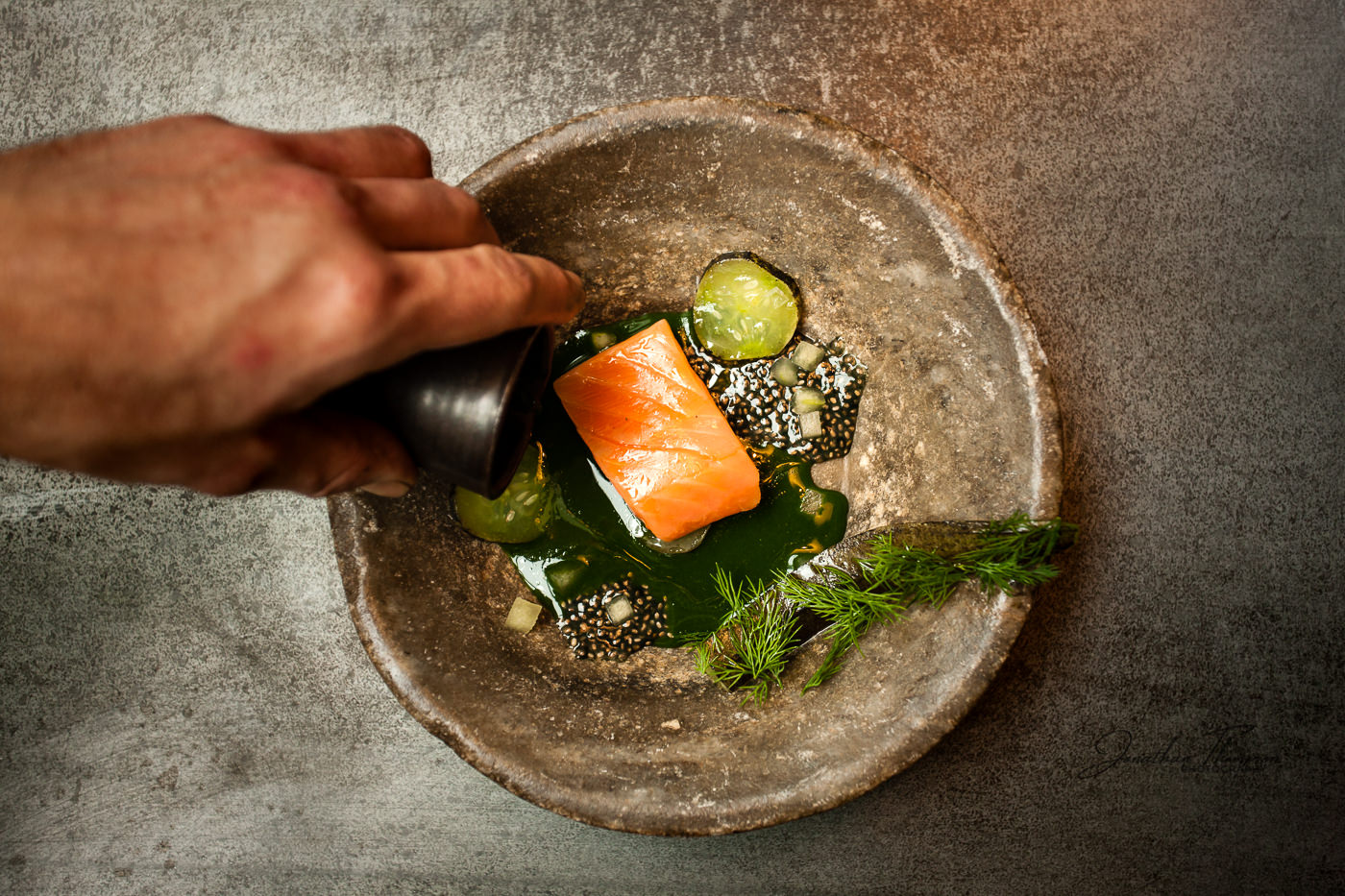 Hand pouring green liquid into a stone bowl containing a fish dish