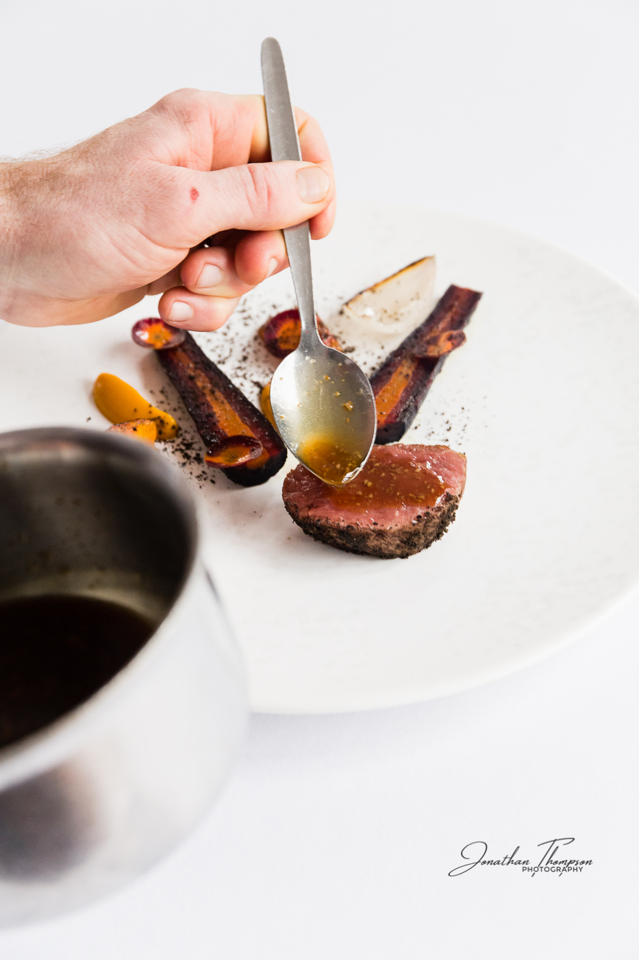 Chefs hand spooning gravy onto a meat and carrot dish served on a white plate