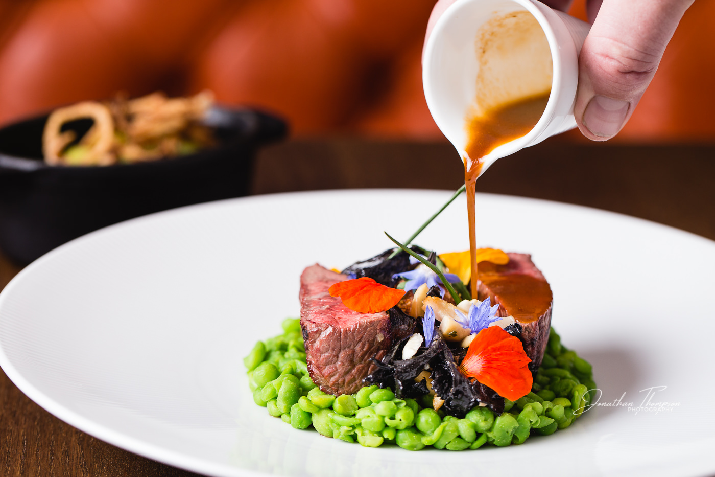 A white jug pouring a gravy onto a meat sitting on a bed of peas and eatable flowers